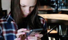 A mulher virada envia um Internet da mensagem ou do uso no telefone que senta-se em um café Vestido em uma camisa de manta fotos de stock royalty free