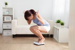 A mulher virada pesa sobre a escala Foto de Stock Royalty Free