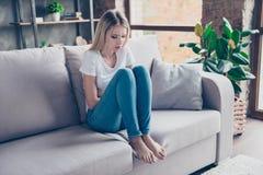 A mulher virada tem primeiros sintomas dos pms Está sentando-se em um sofá imagens de stock