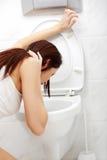 Mulher Vomiting no banheiro. Imagens de Stock