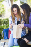Mulheres adolescentes entusiasmado da raça misturada que olham nos sacos  Fotos de Stock