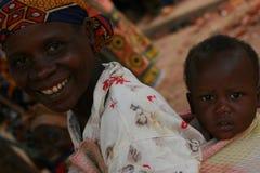Mulheres africanas que carreg crianças Foto de Stock