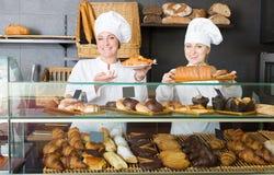 Mulheres alegres com as sobremesas na loja de pastelaria Imagens de Stock Royalty Free