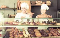 Mulheres alegres com as sobremesas na loja de pastelaria Fotografia de Stock
