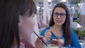 Mulheres alegres dos amigos nos vidros para comunicar e beber cocktail através da palha durante o almoço no café no fim de semana vídeos de arquivo