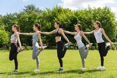 Mulheres alegres que fazem atividades do esporte no parque Imagens de Stock Royalty Free