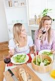 Mulheres alegres que têm o divertimento ao comer a salada fotos de stock royalty free