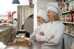 Mulheres alegres que vendem porcas e pastelaria Fotografia de Stock Royalty Free