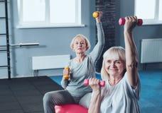 Mulheres aposentadas desportivas que fazem exercícios com pesos no clube de aptidão Imagem de Stock