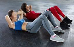 Mulheres aptas novas no gym que faz o exercício do Abs fotos de stock royalty free