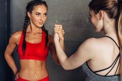 Mulheres aptas que guardam as mãos com um oponente fêmea que olha em seus olhos fotografia de stock