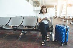 Mulheres asiáticas do viajante que procuram o voo no smartphone no conceito do curso do terminal de aeroporto fotografia de stock