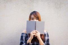 Mulheres asiáticas novas bonitas que escondem atrás de um livro cinzento no fundo do muro de cimento Foto de Stock Royalty Free