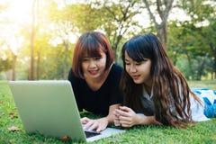 Mulheres asiáticas novas do moderno feliz que trabalham no portátil no parque Estudo na grama fotografia de stock royalty free