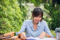 Mulheres asiáticas novas que escrevem trabalhos de casa na mesa dentro fora, mulher que trabalha com conceito feliz da emoção ima Fotografia de Stock