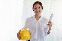 Mulheres asiáticas que projetam guardando os modelos, capacete de segurança para o workin imagens de stock royalty free