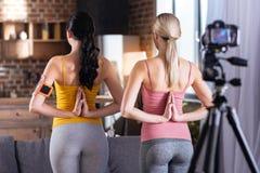 Mulheres bem construídas agradáveis que guardam as mãos atrás de suas partes traseiras Fotografia de Stock Royalty Free