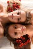 Mulheres bonitas com as pétalas vermelhas da flor Fotografia de Stock