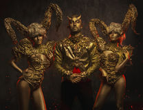 Mulheres bonitas do diabo com os chifres decorativos dourados e o homem considerável do diabo no revestimento decorativo Imagens de Stock Royalty Free