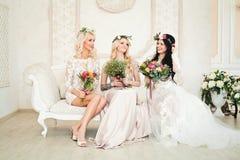 Mulheres bonitas no vestido de noite que senta-se no sofá e no sorriso Foto de Stock