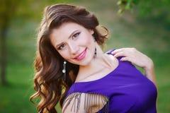 Mulheres bonitas novas com cabelo ventoso longo nos vestidos violetas elegantes que estão na grama verde Foto de Stock