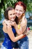 2 mulheres bonitas novas felizes que compartilham do tempo alegre que abraça fora Imagem de Stock Royalty Free