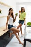Mulheres bonitas que bebem a desintoxicação fresca Juice For Healthy Nutrition Fotografia de Stock