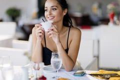 Mulheres bonitas que bebem o chá no restaurante imagem de stock