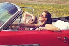 Mulheres bonitas que conduzem accesoriess vestindo de um vintage retro vermelho do carro Fotos de Stock