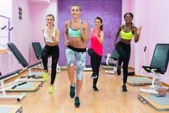 Mulheres bonitas que correm na hora durante a classe do exercício de HIIT dentro imagens de stock