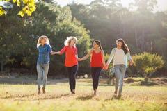 Mulheres bonitas que guardam as mãos e que andam junto no parque foto de stock royalty free