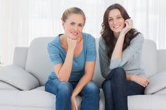 Mulheres bonitas que levantam ao sentar-se no sofá Fotos de Stock Royalty Free