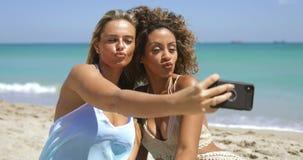 Mulheres brincalh?o que levantam para o selfie na praia filme