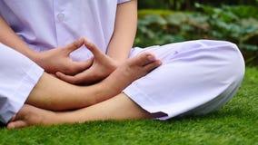 Mulheres budistas que sentam-se para a meditação na corrediça da grama verde que move-se da direita para a esquerda vídeos de arquivo
