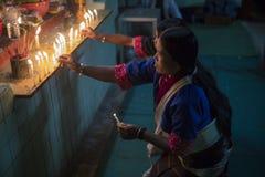 Mulheres burmese que iluminam velas em um altar Imagem de Stock Royalty Free