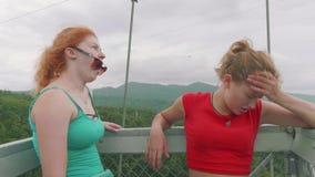 Mulheres caucasianos ruivos e louras para faltar e olhar um vale da montanha de uma ponte de suspensão alta nas montanhas filme