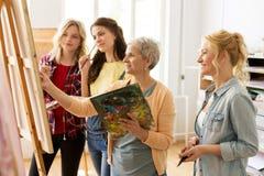 Mulheres com as escovas que pintam na escola de arte Foto de Stock Royalty Free