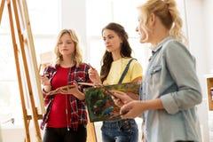 Mulheres com as escovas que pintam na escola de arte Fotografia de Stock Royalty Free