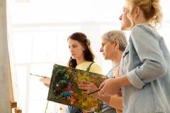 Mulheres com as escovas que pintam na escola de arte Imagem de Stock