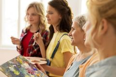 Mulheres com as escovas que pintam na escola de arte Fotos de Stock Royalty Free