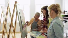 Mulheres com as escovas que pintam na escola de arte filme