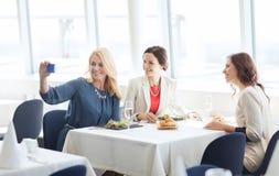 Mulheres com o smartphone que toma o selfie no restaurante foto de stock