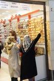 Mulheres com os scarves que escolhem braceletes dourados Fotografia de Stock