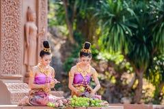 Mulheres com os vestidos tradicionais que dobram a pétala dos lótus Imagem de Stock