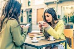 Mulheres com smartphones em uma barra fotografia de stock
