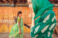 Mulheres com telefones celulares que andam na rua com as paredes coloridas das casas Fotos de Stock