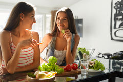 Mulheres comendo saudáveis que cozinham a salada na cozinha Alimento da dieta da aptidão imagem de stock royalty free