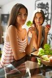 Mulheres comendo saudáveis que cozinham a salada na cozinha Alimento da dieta da aptidão fotografia de stock