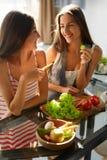 Mulheres comendo saudáveis que cozinham a salada na cozinha Alimento da dieta da aptidão fotos de stock