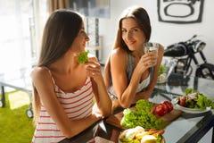 Mulheres comendo saudáveis que cozinham a salada na cozinha Alimento da dieta da aptidão imagens de stock royalty free